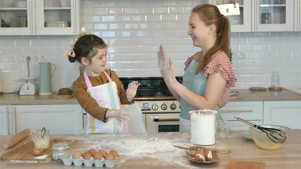 Thumbnail for Girl and Mother Clap Hands with Flour Cooking Cake at Table