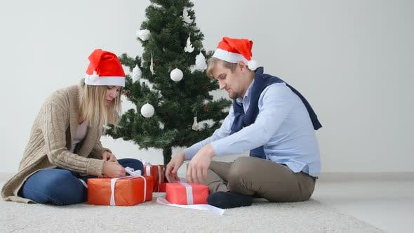 Thumbnail for Concept of Christmas and Happy New Year. Happy Young Couple Opening a Christmas Presents
