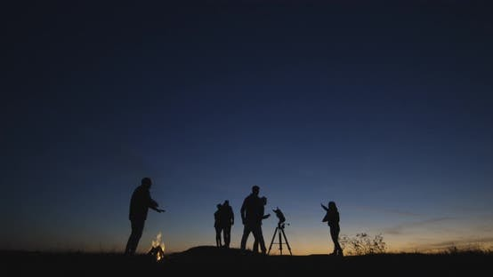 Cover Image for Friends with Campfire Looking Through Telescope in Night