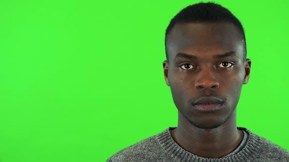 Thumbnail for A Young Black Man Looks at the Camera - Face Closeup - Green Screen Studio