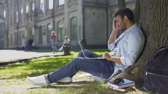 Thumbnail for College Student Sitting Under Tree, Using Laptop Looking Worried, Upsetting News