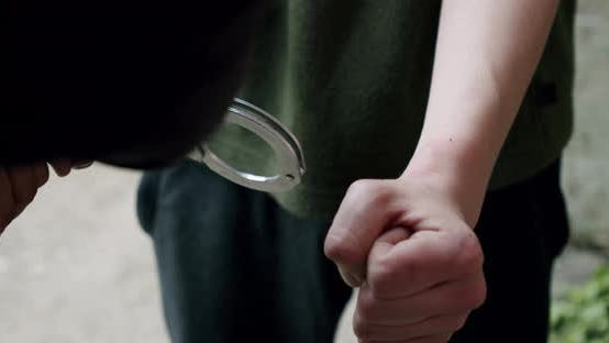 Thumbnail for The Criminal Is Handcuffed and Held in Front Close Up.