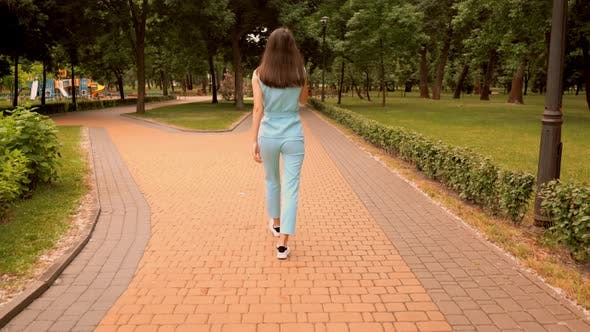 Thumbnail for Back View Cheerful Caucasian Woman Walking Talking By Phone on the Street in City Park