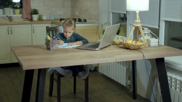 Little Girl Draws On Paper With Pencils Drawings At Home