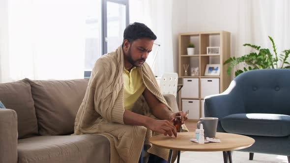 Sick Man Pouring Antipyretic Medicine To Spoon