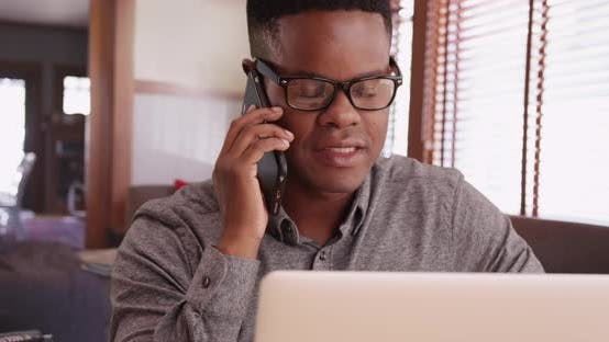 Thumbnail for Black male with glasses talks on the phone working on his laptop