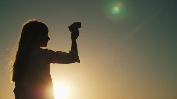 Thumbnail for Profile of a Girl Playing with a Paper Airplane at Sunset