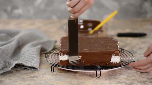 Schokoladenglasur Gießen auf Kuchen. Der Konditorei glasiert einen Kuchen.