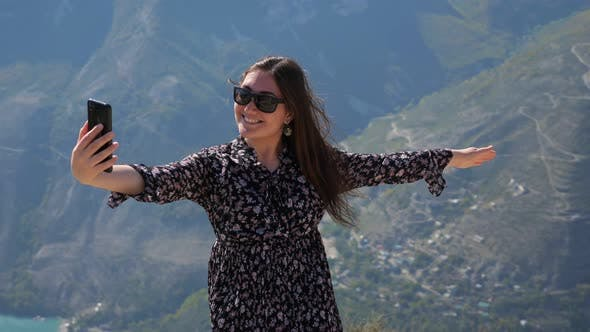 Smiling Lady in Loose Dress Makes Selfie Against Mountains