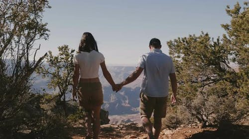 Back View Young Adult Romantic Couple Walk Together Hold Hands To Epic Panoramic View