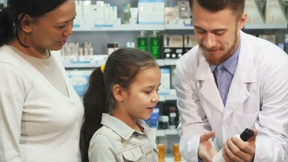 Thumbnail for Friendly Pharmacist Shows Little Girl One of the Tubes