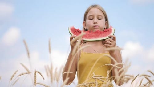 Cute Girl Eating Juicy Watermelon Standing in Wheat Field on Sunny Summer Day