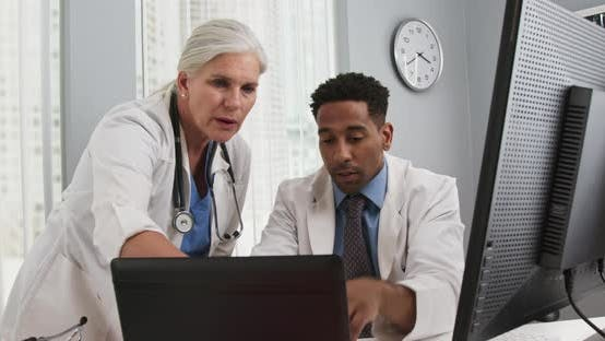 Thumbnail for Close up of two medical professionals working together with technology in office