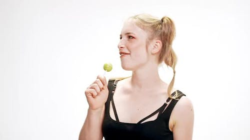 Young Beautiful Girl Dancing Smiling Holding Chupa Chups Singing Over White Background