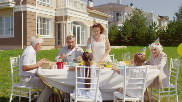 Thumbnail for Family Enjoying Birthday Dinner Outdoors on Sunny Day