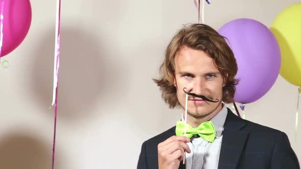 Thumbnail for Party man dancing with mustache and balloons on white background in photo booth