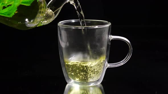 Green Tea Is Being Poured From the Glass Teapot Ona Black Background