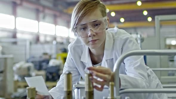 Cover Image for Young Blonde Female Engineer Inspecting Factory Machine