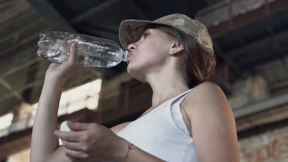 Thumbnail for Portrait of Pretty Young Woman in Military Cap Drinking Water From the Bottle in Dusty Dirty