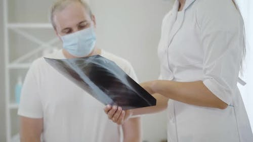 Lungs X-ray in Female Hands with Unrecognizable Doctor Explaining Roentgen To Mid-adult Man in Face