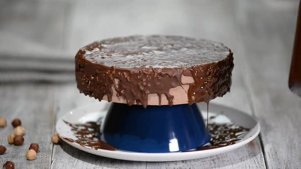 The chocolate icing on the froasted cake.Modern French mousse cake with chocolate glaze.