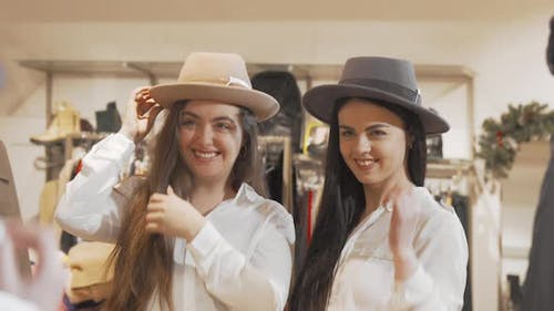 Female Friends Having Fun at Clothing Store Trying Hats Together