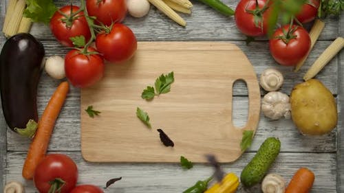 Parsley Piecesfalling on a Cutting Board with Vegetables Around