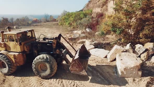 professional bulldozer with a bucket is picking up stones on sand quarry