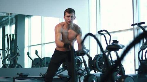 Sportlicher Mann arbeitet mit Battle Ropes
