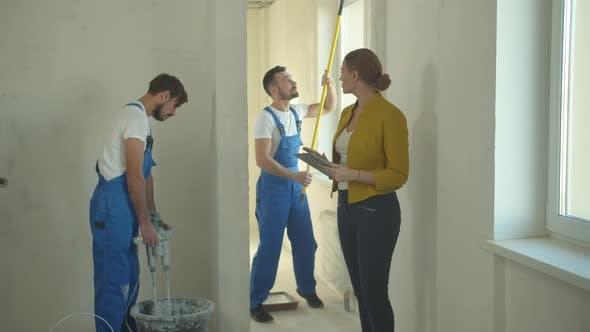 Frau geht mit Tablet und Uhren, wie Bauherren arbeiten