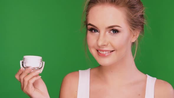 Thumbnail for Young Woman Applying Cream on Her Face and Looking on Cream