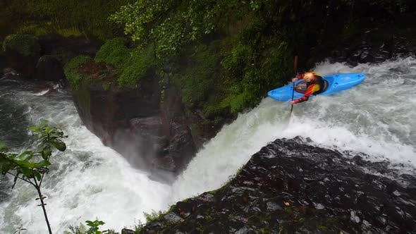 Thumbnail for A man paddles his kayak down a waterfall on river rapids.