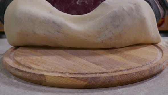 Nahaufnahme eines Küchenchefs, der italienische Pizza kocht. Der Prozess der Herstellung von Pizza am Tisch. Frisch