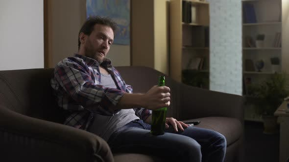 Thumbnail for Drunk Male Sitting on Couch and Talking to Bottle of Beer, Addiction to Alcohol
