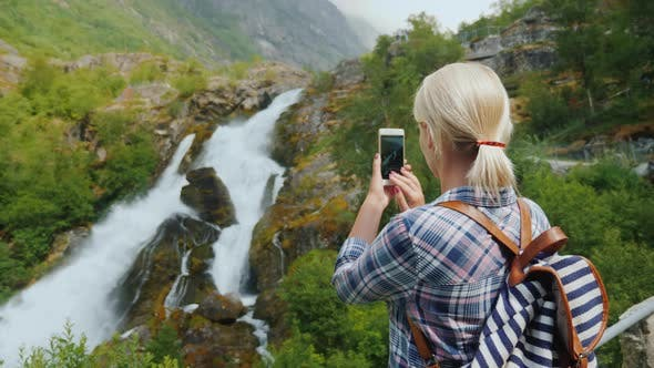 Thumbnail for Female Traveler Takes Pictures of a Picturesque Waterfall in Norway