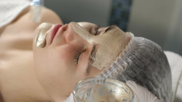 Modern Beauty Concept. Beautician Applying Cosmetic Golden Mask on Beautiful Female Face Skin