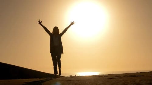 Woman in Business Attire Raising Her Arms Embracing Freedom During Sunset