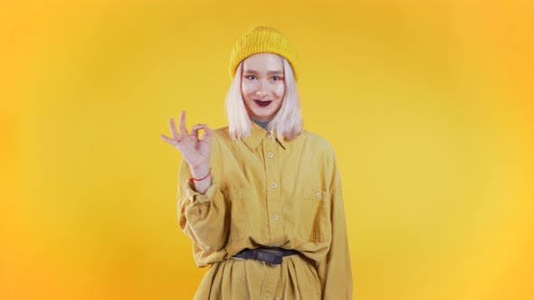 Thumbnail for Positive Girl Making OK Sign Over Yellow Background and Smiles To Camera.