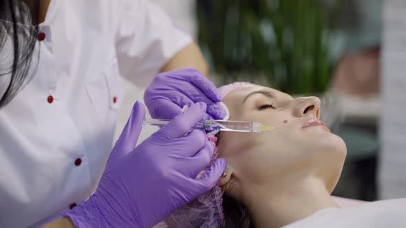 An Experienced Cosmetologist Conducts Mesotherapy for a Woman