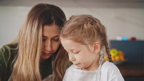 Mother and Little Girl with Long Hair are in Kitchen