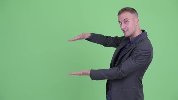 Cover Image for Happy Handsome Businessman in Suit Snapping Fingers and Showing Something