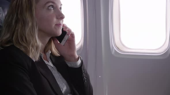 Thumbnail for Businesswoman talking on cell phone on airplane