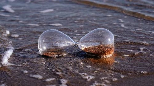 Waves Wash Sandglass Lying on Sand at Bright Summer Sunlight