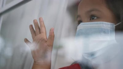 Asian girl wearing a surgical mask is looking out of the window and touching window.