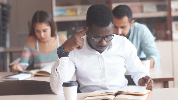 Thumbnail for African American Male College Student Wearing Spectacles Preparing for Exams in Library, Reading