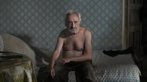 Beggar Man Sitting on a Bed
