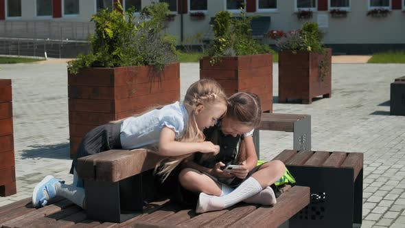Kids Playing With Mobile Phone In Schoolyard