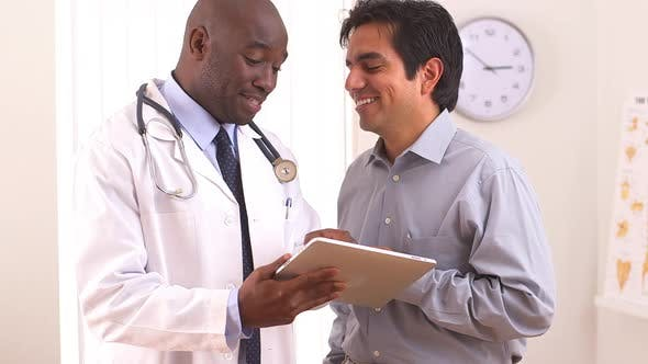 Thumbnail for African American doctor using tablet pc with Hispanic patient
