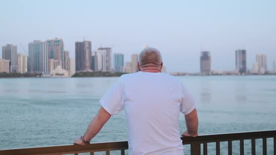 Cover Image for Senior Man Looking at the Bay Standing on the Waterfront Rear View Looking at the Beautiful View