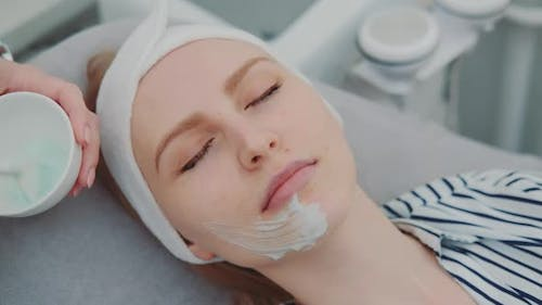 Cosmetician Hands Applying Cream Mask on Young Woman's Face at Beauty Spa Salon